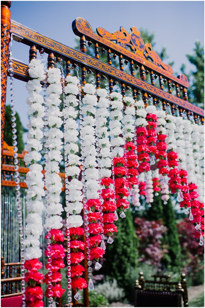 A Hindu style wedding ceremony backdrop with white and red flowers, a crystal strands hanging from a wood arch with traditional carvings, Dairyland wedding, Snohomish county wedding, Hindu wedding, wedding planning by Perfectly Posh Events, Photo by Barrie Anne Photography