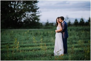 Bride and groom share an embrace in a Christmas tree field as the sun sets in the background, Dairyland wedding, Snohomish county wedding, Hindu wedding, wedding planning by Perfectly Posh Events, Photo by Barrie Anne Photography