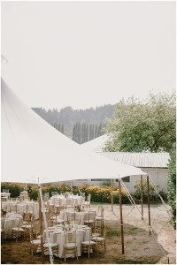 A large white tent set up outdoors with white dinner tables topped with floral center pieces and surrounded by gold chairs, DeLille Cellars winery, Woodinville Washington wedding, event planning by Perfectly Posh Events , Photo by Kristen Marie Parker