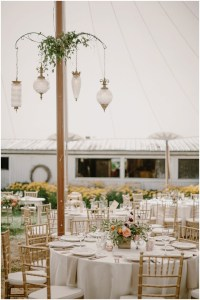 A large white tent set up outdoors with white dinner tables topped with floral center pieces and surrounded by gold chairs and vintage glass lamps hanging from the pillar, DeLille Cellars winery, Woodinville Washington wedding, event planning by Perfectly Posh Events , Photo by Kristen Marie Parker