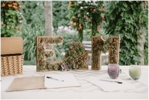 Wedding guest sign-in booking sits atop a table with custom made letters of the couple's initials filled with succulents and accessorized with purple and green Glassy Baby candle holders, DeLille Cellars winery, Woodinville Washington wedding, event planning by Perfectly Posh Events , Photo by Kristen Marie Parker
