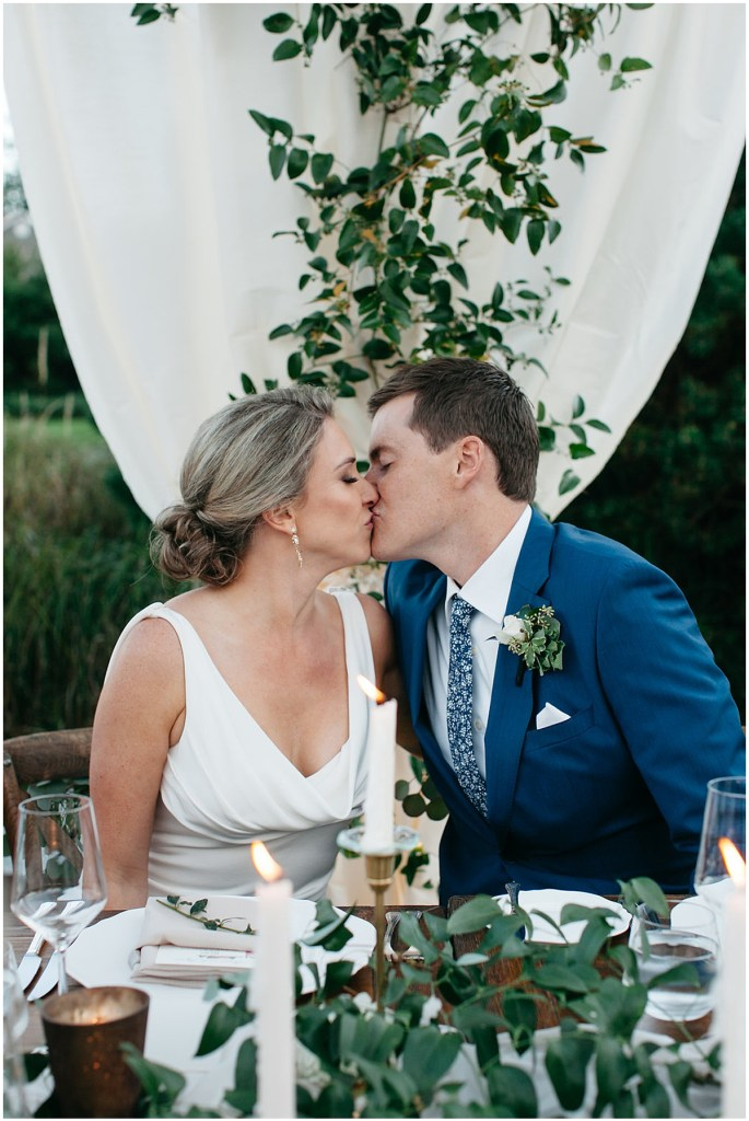 PNW outdoor summer wedding by Washington wedding designer Perfectly Posh Events. The bride and groom share a kiss during their wedding reception. Photo by Kate Price Photography.