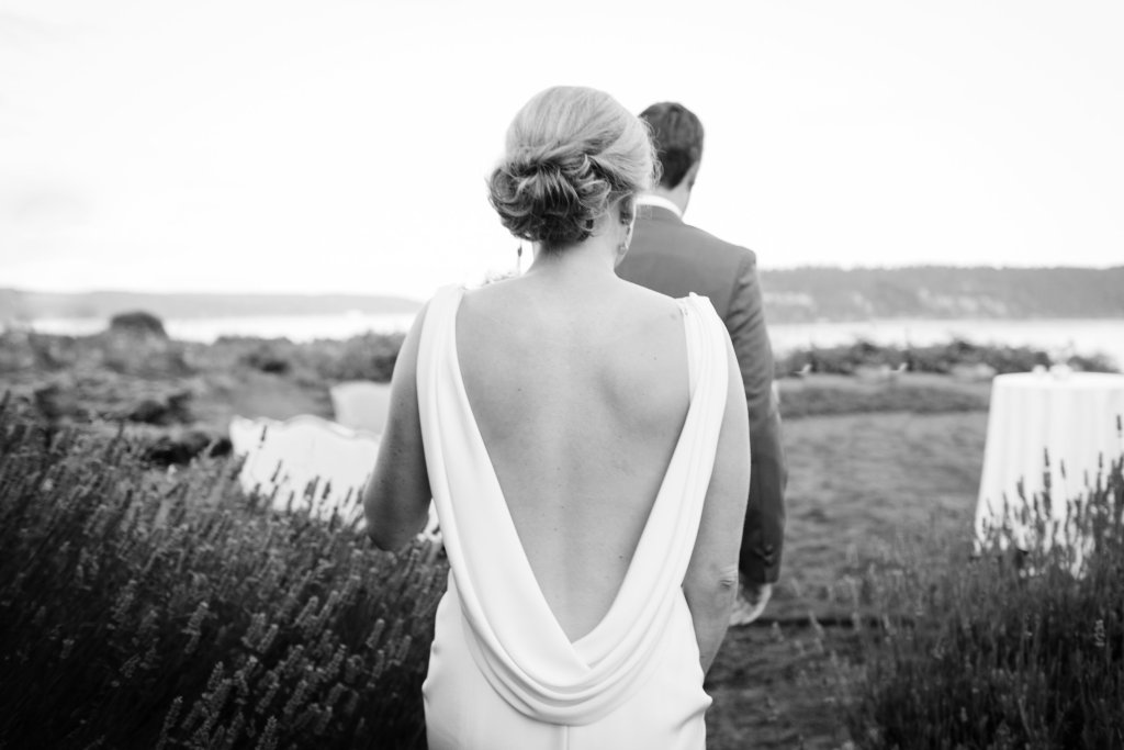 A bride in a stunning backless wedding gown featuring soft draping. PNW outdoor summer wedding by Washington wedding designer Perfectly Posh Events. Photo by Kate Price Photography.