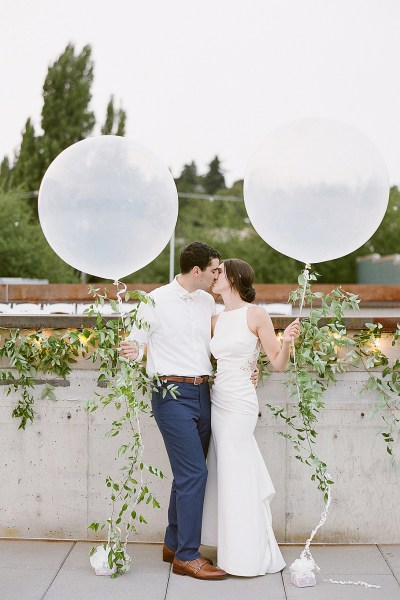 Fun white & translucent balloons at this modern classic wedding on the rooftop at Fremont Foundry! Click for more wedding inspiration from this light + airy wedding in Seattle at wedding venue Fremont Foundry. Event planning by Perfectly Posh Events, based in Seattle and Portland. Wedding photography by Katie Parra Photography. #perfectlyposhevents
