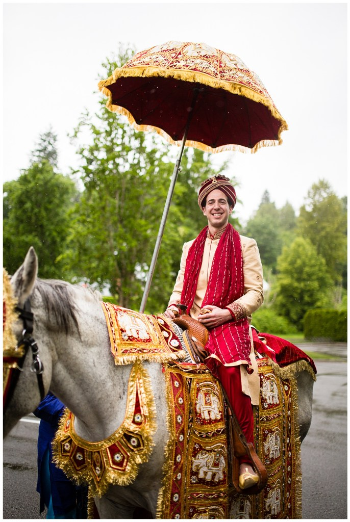 Jake rides atop a horse donned in traditional and colorful Indian wear as he gets ready to lead his wedding guests in the baraat at Columbia Winery in the rain.