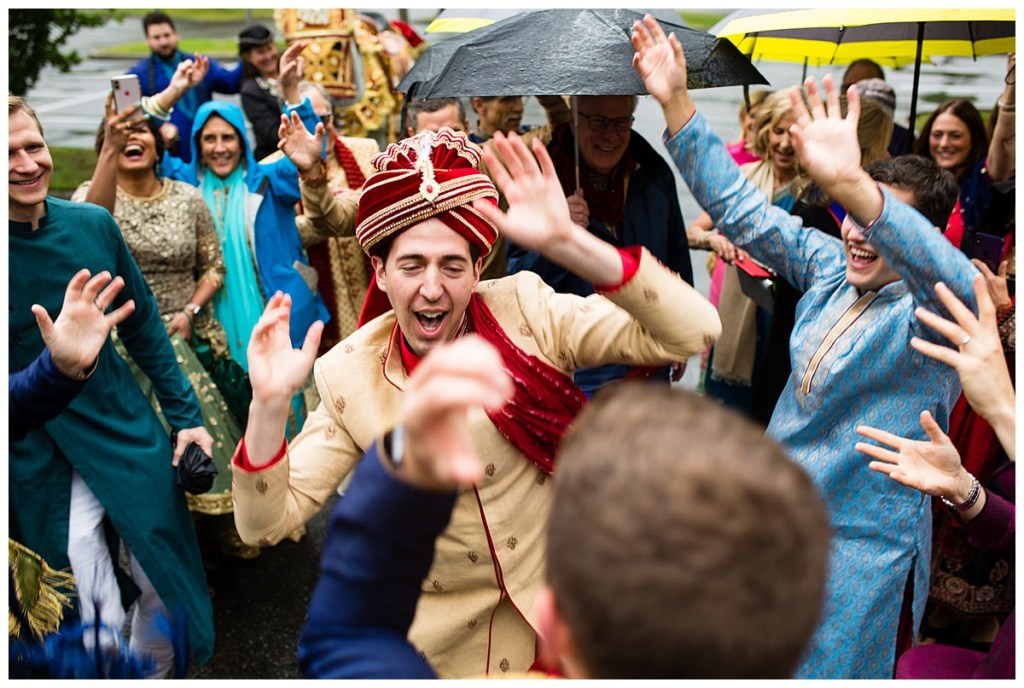 Jake and his guests, donned in traditional and colorful Indian wear, dance in the rain as part of Jake's baraat at Columbia Winery.