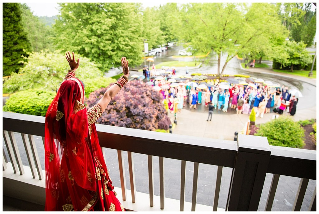 Hetal waves to her wedding guests from the balcony above as they are donned in traditional and colorful Indian wear as part of Jake's baraat at Columbia Winery.