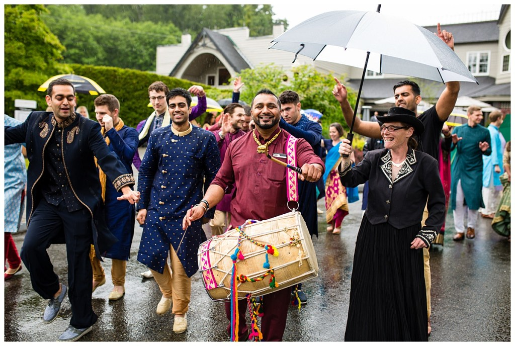 A dohl drummer leads Jake and his guests, donned in traditional and colorful Indian wear, in the rain as part of Jake's baraat at Columbia Winery.