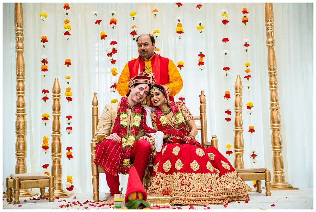 Hetal + Jake share a sweet moment with the priest as they are seated on top of the mandap that is decorated with bold and vibrant carnations for their traditional Indian wedding ceremony.