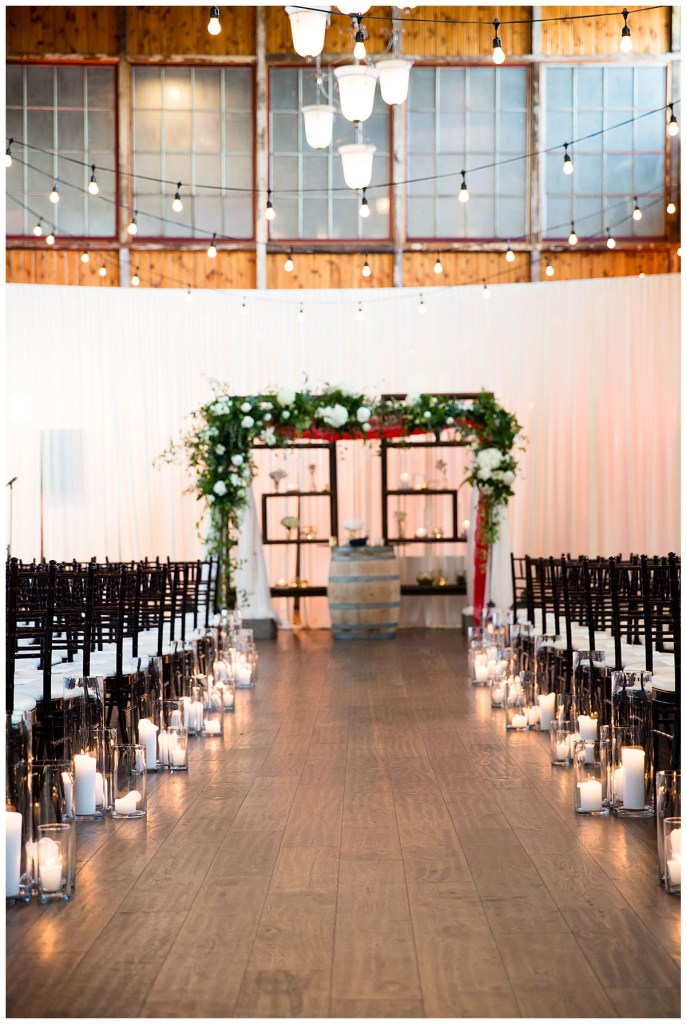 White florals and greenery deocrated the chuppa as candles decorated the ceremony aisle. Hetal's mother's red sari was incorporated into the into the chuppa as Hetal + Jake blended their two cultures together on their wedding weekend.