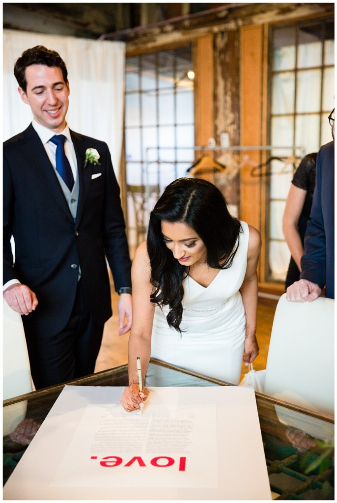 "Hetal + Jake sign the ketubah, a Jewish wedding contract, featuring the word ""love"" in a bold and vibrant red."