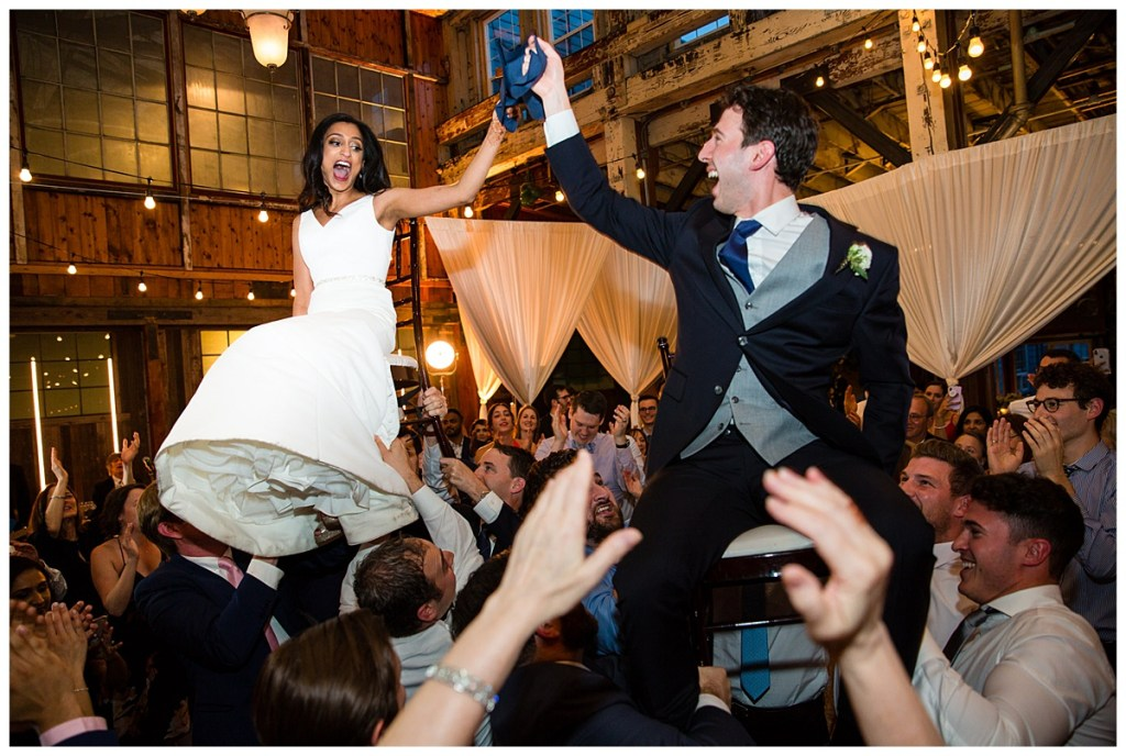 Hetal + Jake's wedding guests lifted them up into the air as they sat on chairs during the dance party.