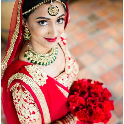 Hetal shows off her red and gold wedding sari along with her traditional Indian jewelry and her bold bridal bouquet on her wedding day.