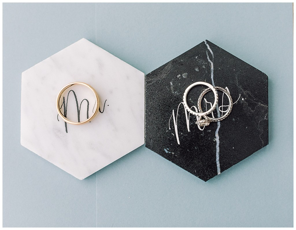 Elena + Travis's wedding bands and Elena's rings are pictured on their place cards, a geometric shape with hand calligraphy.