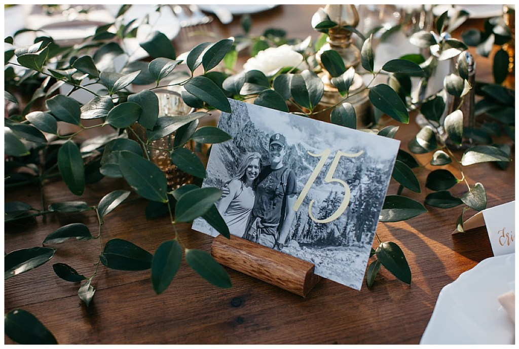 Wedding reception table numbers feature photos of couple with gold and greenery.