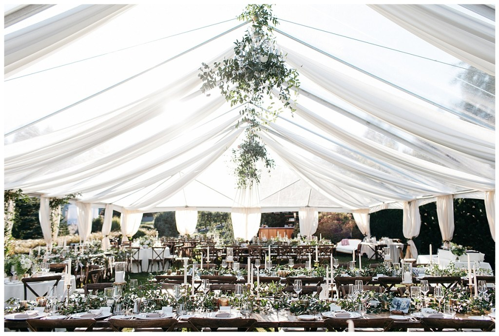 Wedding reception tent with greenery wrapped around chandeliers and wood tables and chairs.