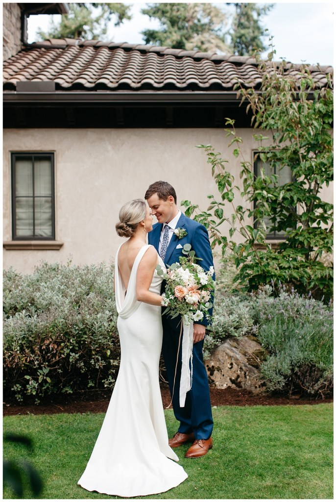 Sleeveless backless white wedding dress and navy suit with brown shoes.