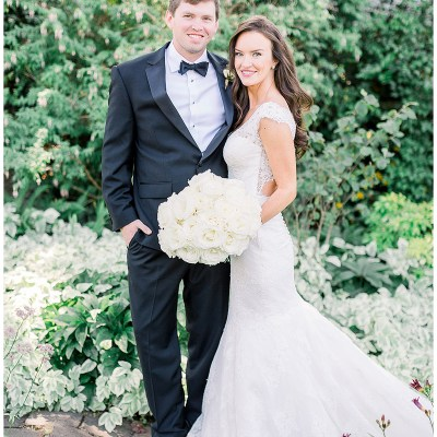 Monochromatic white bridal bouquet and white lace wedding dress with classic black tuxedo.
