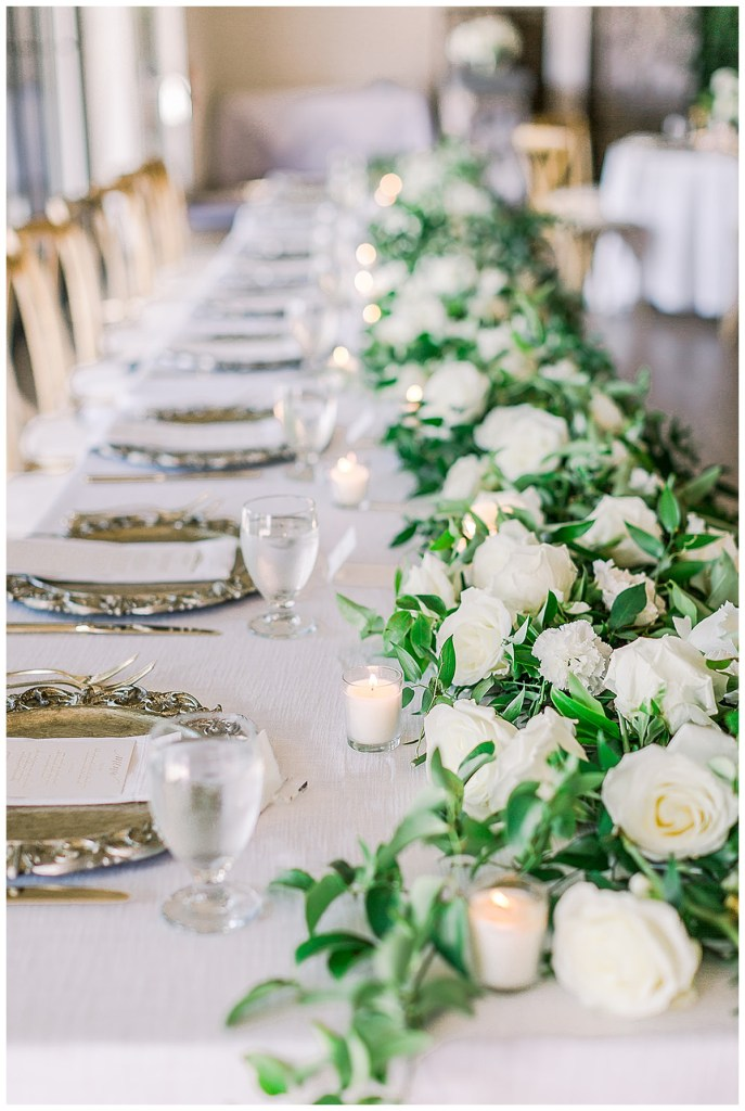Greenery garland with white roses tucked in for wedding reception table and votive candles.