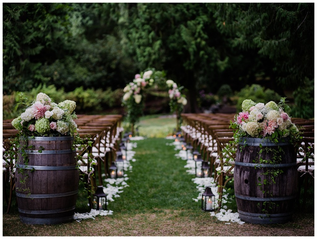 Lush pink and white aisle markers on wine barrels with cascading greenery and rustic lanterns. Click for more luxurious and lush PNW design from this Chateau Lill wedding in Woodinville, WA. Wedding planning by Perfectly Posh Events, based in Seattle. Wedding photography by Shane Macomber Photography. Wedding Flowers by Flora Nova Design. #perfectlyposhevents