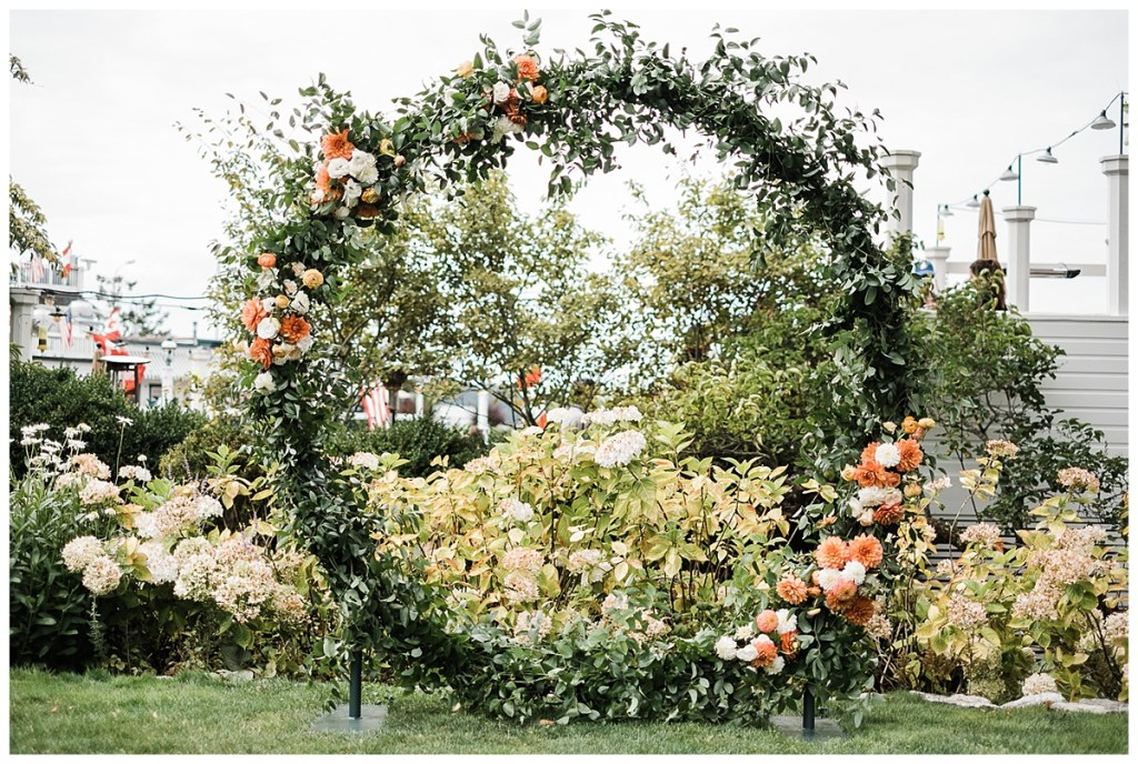 Wedding ceremony circle arch with greenery and orange and white flowers.