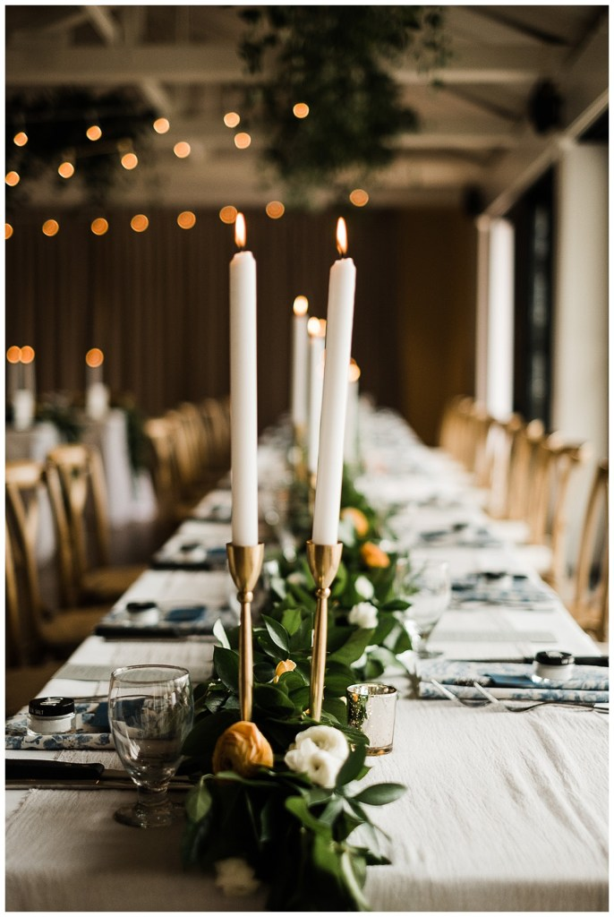Wedding reception table garland with orange and white flowers with white taper candles and brass candleholders.