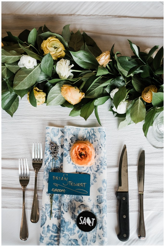 Modern wedding reception place setting with blue and white napkin and garland with orange and white flowers.