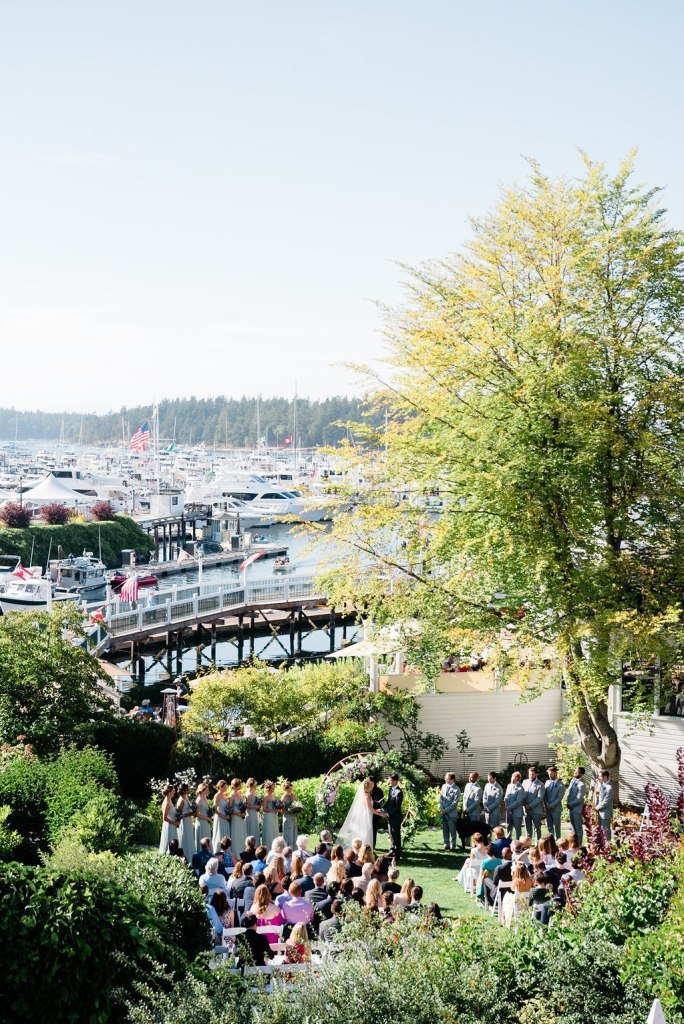 Roche Harbor Resort ceremony out on lawn overlooking Roche Harbor Marina. Click for more PNW island wedding design from this San Juan Island wedding at Roche Harbor Resort in San Juan Island, WA. Wedding planning by Perfectly Posh Events, based in Seattle and Portland. Wedding photography by Lloyd Photographers. Flowers by Bloom San Juan. #perfectlyposhevents