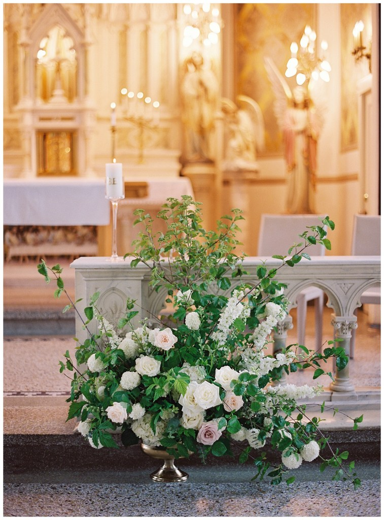 Tall floral wedding altar centerpiece with greenery and white and blush flowers.