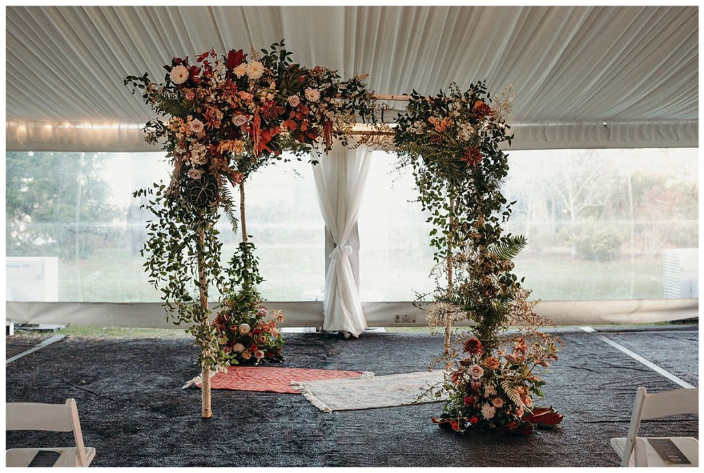 Boho style wedding chuppah with dark and dramatic blooms and boho style rugs.