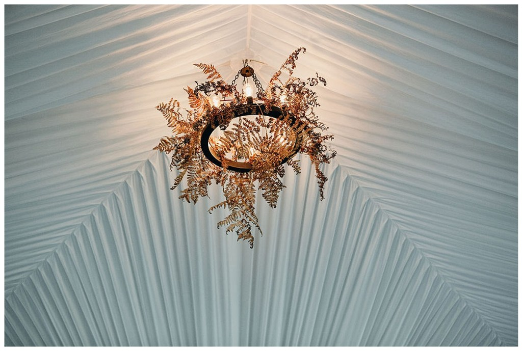 Wedding ceremony tent with boho dried greenery on chandeliers.