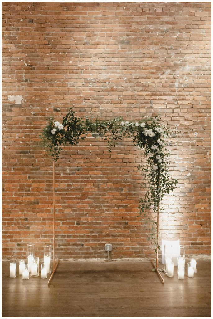 Minimal copper arch against brick wall for wedding ceremony. Click to see more from this urban loft wedding design for in wedding at Axis Pioneer Square in Seattle, WA. Wedding planning by Perfectly Posh Events, based in Seattle. Wedding photography by Carina Skrobecki Photography. Flowers by Rusted Vase Co. #perfectlyposhevents