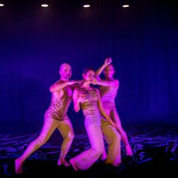 three dancers in pink light on stage