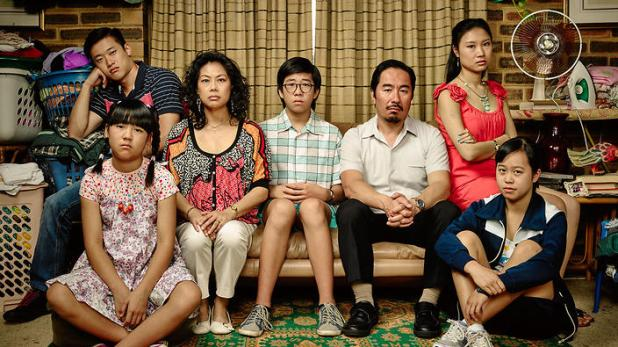 A Chinese family of seven sits on the couch in a suburban home. They are posing as though for a family photo, but are clearly mid-conflict.