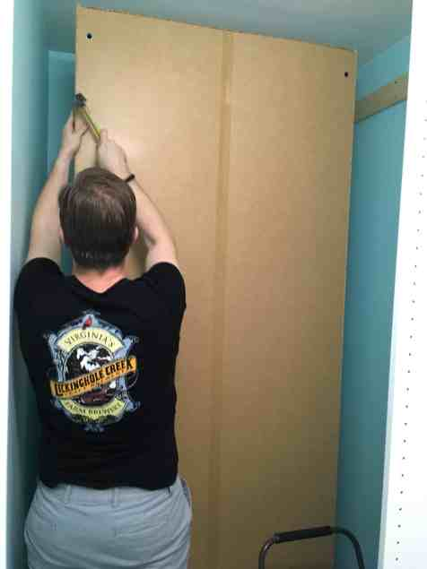 Mr. PC nailing backing to wardrobe