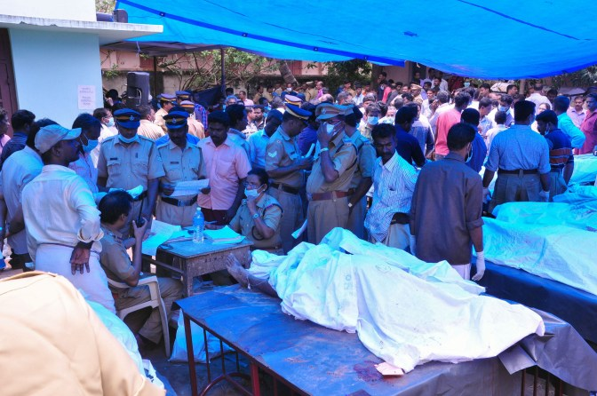 Indian officals stand next to bodies kept outside of a hospital as relatives try to identify victims of a huge fire at the Puttingal Devi Temple in Paravur on April 10, 2016. A massive fire swept through a temple in the southern Indian state of Kerala on April 10, killing more than 100 people and injuring at least 280 after thousands gathered to watch a fireworks display.  / AFP / -        (Photo credit should read -/AFP/Getty Images)