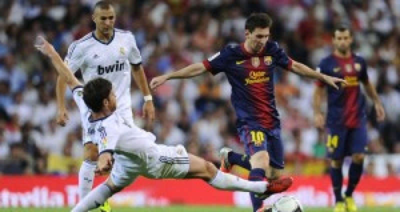 MADRID, SPAIN - AUGUST 29:  Lionel Messi of FC Barcelona (R) duels for the ball with Xabi Alonso of Real Madrid CF during the Supercopa second leg match betwen Real Madrid and FC Barcelona at Estadio Santiago Bernabeu on August 29, 2012 in Madrid, Spain.  (Photo by David Ramos/Getty Images)