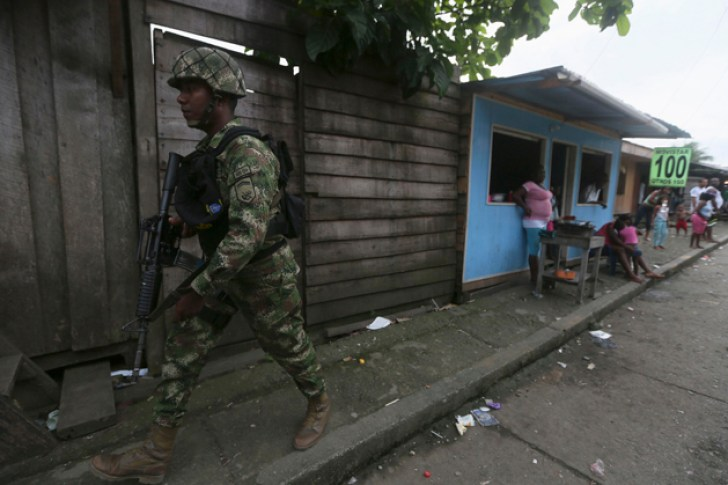 """A Colombian Special Forces soldier patrols a street in the """"La Playita"""" neighbourhood, during a visit by Defence Minister Juan Carlos Pinzon in the port city of Buenaventura March 21, 2014. Human Rights Watch has called on Colombian authorities to step up security in the violence-ravaged port city of Buenaventura after a crime wave forced thousands of residents to flee their homes.  REUTERS/John Vizcaino  (COLOMBIA - Tags: MILITARY CONFLICT POLITICS CIVIL UNREST CRIME LAW)"""