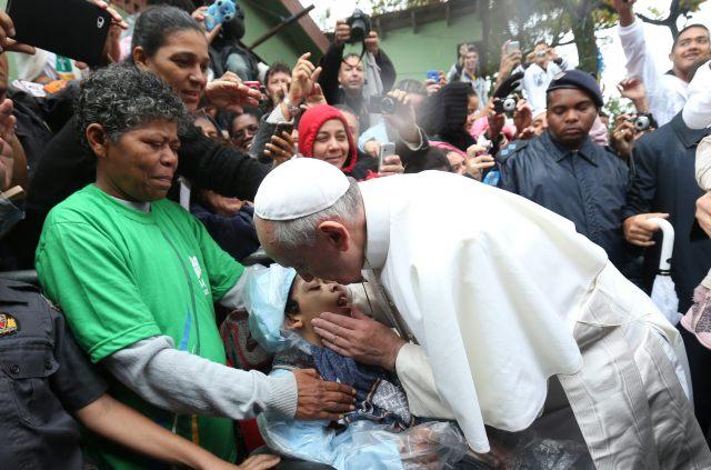 """BRA129. RÍO DE JANEIRO (BRASIL), 25/07/2013.- El papa Francisco besa a un niño hoy, jueves 25 de julio de 2013, durante su visita a la favela Varginha en Río de Janeiro (Brasil). El pontífice visitó hoy una favela, donde dijo que """"nadie puede permanecer indiferente ante las desigualdades que existen en el mundo"""". Además, en su visita el complejo de favelas de Manguinhos, en la zona norte de Río de Janeiro, donde viven unas 2.000 personas en casas hechas con cartón y materiales de derribo, pidió a los poderes públicos que trabajen por un mundo más justo y solidario y a los jóvenes que luchen contra la corrupción y la injusticia. EFE/Antonio Lacerda"""