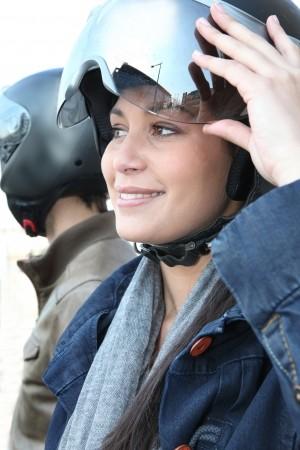 Una mujer que da vuelta a su visera del casco de motocicleta. Auremar, 123RF