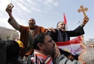 Plaza Tahrir, un musulmán alza el Corán, un copto la Cruz