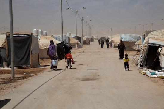 Esta calle, que atraviesa el campamento de refugiados de Zaatari, en Jordania, fue nombrada Campos Elíseos. Hombres árabes se acercan para comprar vírgenes. Crédito: Liny Mutsaers/IPS.