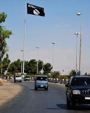 Vehículos en la entrada de la ciudad de Raqqa, Siria oriental, junto a una bandera de Al Qaeda 04 de octubre 2013. © REUTERS/Nour Fourat