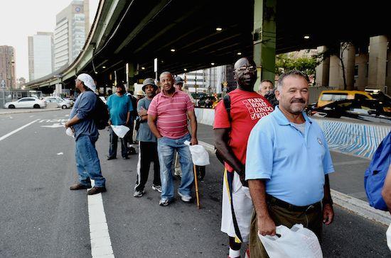 Hombres en fila para recibir alimentos distribuidos por voluntarios de la Coalición para los Sin Techo, en la ciudad de Nueva York. Crédito: Zafirah Mohamed Zayn/IPS