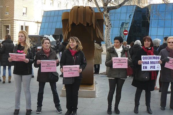 Protestas de mujeres ante la estatua de la mujer víctima de la violencia machista. Fotografía publicada en Crónica de Aragón