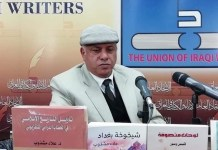 El escritor iraquí, Alaa Mashzoub, junto a algunas de sus obras.