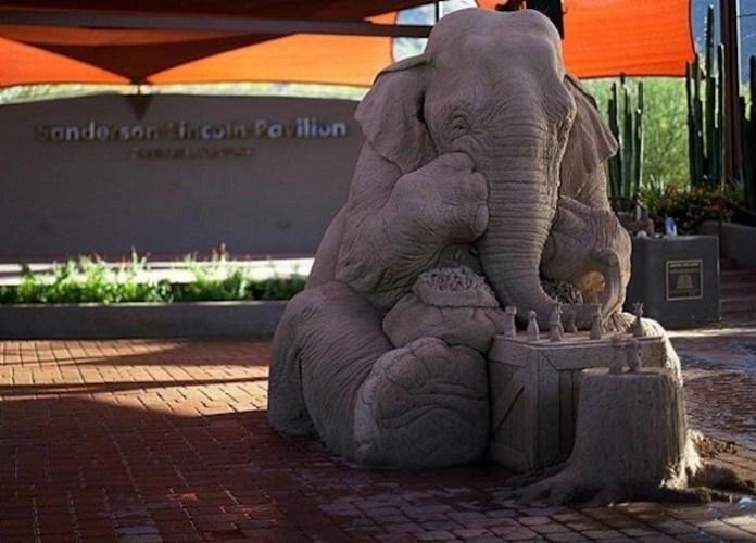 Escultura de arena donde un elefante de tres metros juega con un ratón al ajedrez.
