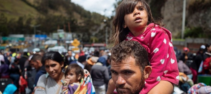 UNICEF/Arcos Laila Dalila León, de tres años, mira hacia la aduana colombiana en Rumichaca, en el frontera entre Colombia y Ecuador, sentada sobre los hombros de su padre.