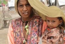 PNUD/Hira Hashmey: Una mujer cubre a su hija para protegerla del calor extremo en Sindh, Pakistán.