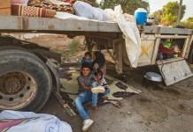 © UNICEF/Delil Souleiman: Una mujer y sus hijos se sientan debajo de un camión a medida que personas desplazadas desde Ras al Ain llegan a Tal Tamer huyendo de la violencia.